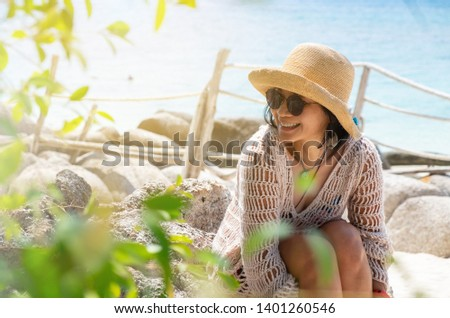 Upper section portrait of an Asian woman with smiling face in her beachwear with hat and sunglasses sitting on a rocky white sand beach with blue sea in the background on her vacation on an island.