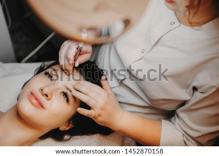 Upper view lovely female face leaning on a spa bed with eyes opened doing noninvasive microdermabrasion on her face by a cosmetologist in a spa center.