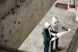 Upper view of a adult arhitecht and his worker talking about building in constructiion being on the worksite.
