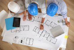 Upper view of architects working on blueprint