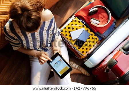 Upper view of elegant woman in white pants and striped blouse at modern home in sunny summer day using mobile app hotel booking near open travel suitcase.
