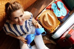 Upper view of elegant woman in white pants and striped blouse in the modern living room in sunny summer day packing bikini in open travel suitcase.