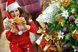 Upper view of happy modern woman with long brunette hair wearing red white Christmas sweater and elf santa hat under decorated Christmas tree near present boxes eating hamburger.