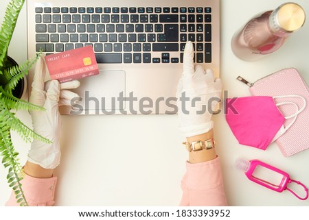 Upper view of woman hands in white rubber gloves browsing online shop on a laptop near medical mask, an antibacterial agent and wallet on white table.