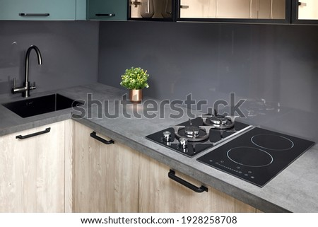 Upscale modern flat design Aqua Menthe kitchen in luxury home with induction electric hob flat oak or walnut wooden panels with flower in vase and sink with tap mixer of modern design. Photo stock ©