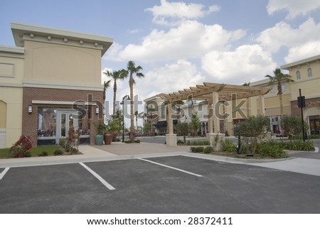 upscale shopping mall with tropical landscaping and pergola