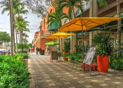 Upscale Tropical Naples Florida Small Tourist Town Vacation Destination Beautiful Quaint Daytime Street Scene with Umbrellas, Sidewalk Restaurant Menus, Decorative Plants and Palm Trees