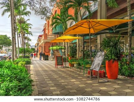 Upscale Tropical Naples Florida Small Tourist Town Vacation Destination Beautiful Quaint Daytime Street Scene with Umbrellas, Sidewalk Restaurant Menus, Decorative Plants and Palm Trees