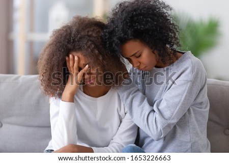 Upset african american mom sister hugging sad child teen girl consoling supporting or asking for forgiveness after fight, black mother hugging comforting depressed teenage daughter sitting on sofa