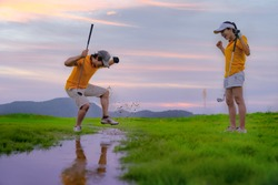 upset and angry of a man golf player steps drub or stamp on the water splash after found a golf ball hit dropped in the water hazard difficult area, golf-mate or competitor cheerfully  mock up beside