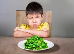 upset and disgusted hispanic kid sitting on table in front of spinach plate unhappy rejecting the fresh food finding it disgusting in child hate green vegetables concept and healthy nutrition
