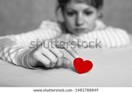 Upset and sad girl is touching red heart with finger while thinking about unrequited love or breakup. All is black-and-white except heart. Focus and accent are on heart. Relationship and love concept