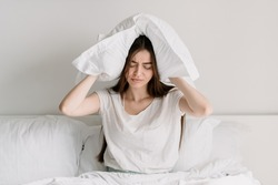 Upset and tired young woman sitting on bed in pajamas, covers ears with a pillow, drowns out the noise. Dissatisfied and unhappy female spending early morning in bedroom at home