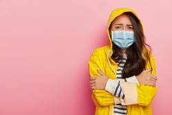 Upset Asian woman trembles from cold, has virus transmitted through airbone droplets, wears protective medical mask, yellow raincoat with hood, stands against pink wall, has contagious disease