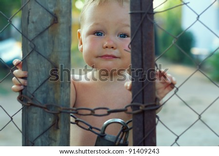 upset baby boy looking out of locked wire fencing. outdoors