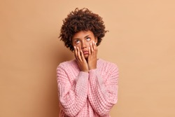 Upset bored Afro American woman keeps hands on cheeks suffers from boredom doesnt know what to do has dull expression stays at home alone dressed in casual sweater isolated over beige background