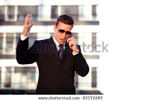 Upset businessman talking over the phone in front of an office building