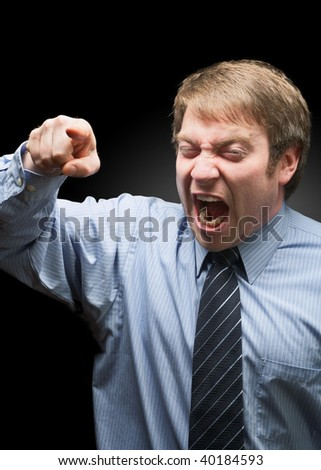 Upset businessman yelling on dark background focus on face
