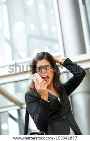 Upset businesswoman screaming crazy on phone. Anxious woman on business problems and crisis receiving bad financial news on smartphone. Hispanic executive suffering stress, panic and anxiety attack.