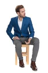 Upset casual man sitting and leaning on his leg while looking to the side concerned and sitting on a chair on white studio background