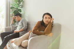Upset couple at home. Handsome man and beautiful young woman are having quarrel. Sitting on sofa together. Family problems.