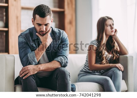 Upset couple at home. Handsome man and beautiful young woman are having quarrel. Sitting on sofa together. Family problems. #742041298