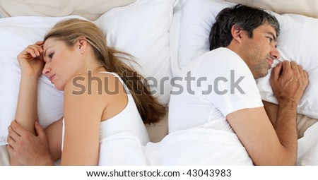 Upset couple sleeping separately on their bed