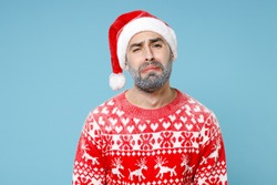 Upset crying Northern bearded man frozen icy snow face in Santa hat Christmas sweater looks camera isolated on blue background in studio. Happy New Year celebration merry holiday winter time concept