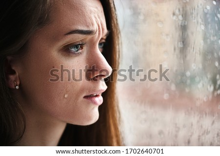 Upset crying woman with tears eyes suffering from emotional shock, loss, grief, life problems and break up relationship near window with raindrops. Female received bad news
