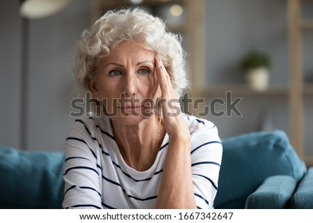 Upset depressed elderly woman sit on couch look in window distance pondering having problems, unhappy mature 60s lady feel lonely lost in thoughts morning or yearning in retirement house