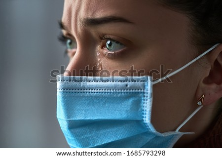 Upset depressed melancholy sad crying woman in protective face mask with tears eyes during serious illness, coronavirus outbreak and flu covid-19 epidemic. Health problems difficulties