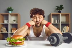Upset depressed young male athlete looking at dumbbell and tempting burger choosing either sport or fast food. Weight loss, fitness, will power, choice between healthy and unhealthy lifestyle concept