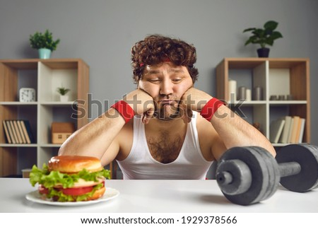 Upset depressed young male athlete looking at dumbbell and tempting burger choosing either sport or fast food. Weight loss, fitness, will power, choice between healthy and unhealthy lifestyle concept Stockfoto ©