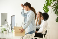 Upset dismissed young woman employee packing box at workplace on last working day, depressed stressed frustrated office worker preparing to leave after getting fired from job or laid off concept