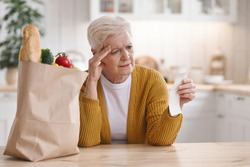 Upset elderly woman with paper bag with food checking grocery check and touching her head, sitting alone in kitchen, copy space. Old lady got shocked with high prices for grocery