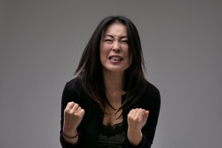 Upset emotional Asian woman clenching her fists in anguish as she implores the viewer or is overcome by loss against a grey studio background with copyspace