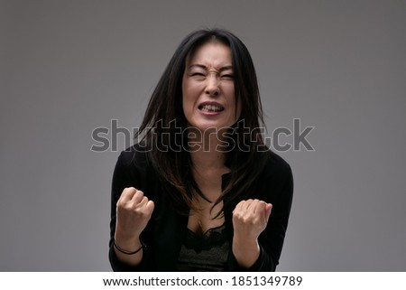 Upset emotional Asian woman clenching her fists in anguish as she implores the viewer or is overcome by loss against a grey studio background with copyspace Foto stock ©