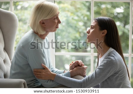 Upset empathic young lady sitting near chair, holding hand of desperate unhappy middle aged mommy, showing support and care. Side view grown up daughter giving psychological help to stressed mom.
