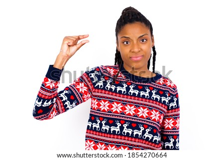 Upset Excited Young beautiful African American woman wearing Christmas sweater, against white wall shapes little gesture with hand demonstrates something very tiny small size. Not very much