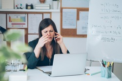 Upset female professor talking on mobile phone on break with online class. Tired teacher is working from home, complaining on phone, angry and displeased with teleconferencing and e-learning students