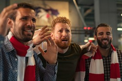 Upset friends watching sport game on TV. Supporters worrying about favourite football team. Soccer fans watching game in disbelief while their team losing the match.