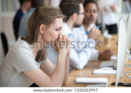 Upset frustrated and confused female worker folding hands on chin feels puzzled having problem troubles and doubts about business moments, sitting in shared modern office with multinational coworkers