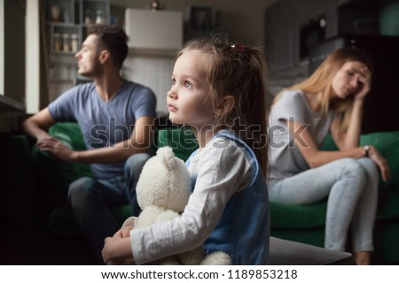 Upset frustrated little girl tired of parent fight, toddler daughter holding toy dreaming that family conflicts would stop, suffering from mother and father quarrels, bad family relationship, break up #1189853218