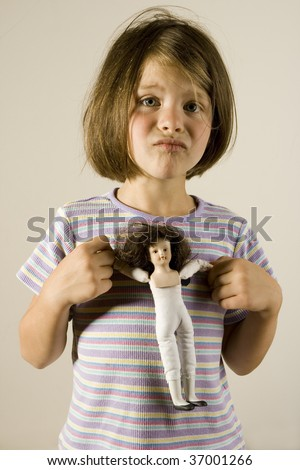 upset girl holding vintage doll