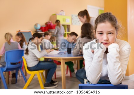 Upset girl standing at a schoolroom on background with pupils studying with teacher  #1056454916