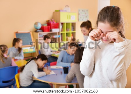 Upset girl standing in the schoolroom on background with pupils studying with teacher  #1057082168