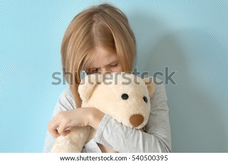 Upset girl with teddy bear on blue background