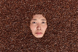 Upset gloomy woman shows only face through coffee beans background unhappy to have addiction to caffeine feels dejected looks doleful. Negative emotions. Human face aroud natural brown seeds