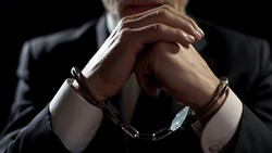 Upset handcuffed man imprisoned for financial crime, punished for serious fraud