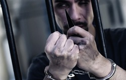 Upset handcuffed man smoking with a knife imprisoned for crime, punished for serious villainy. Horizontal image.